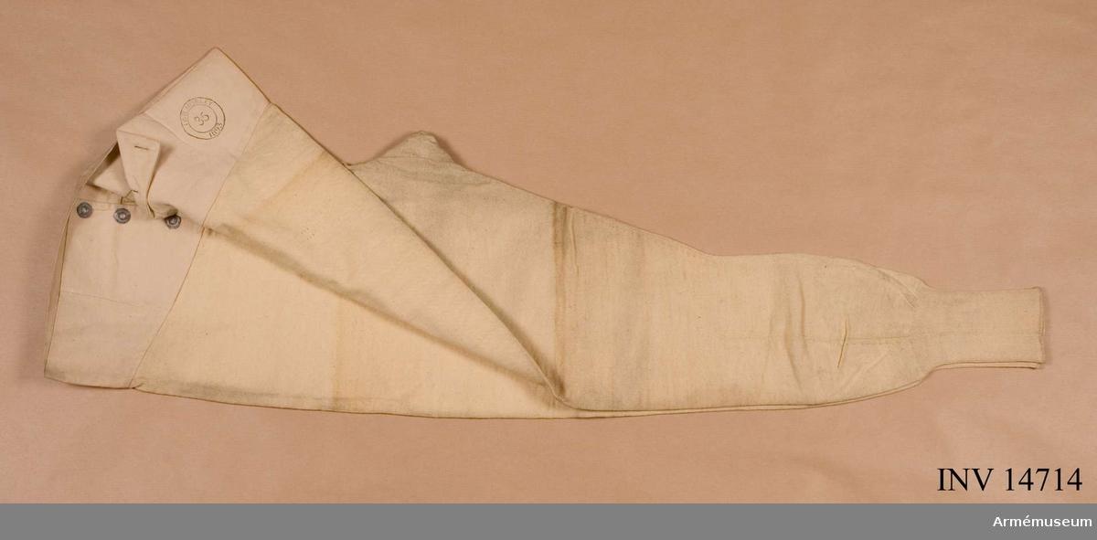 """Grupp C I Av bomullstrikå. Övre del av vitt bomullstyg, som stänges vid  sprundet med 3 järnknappar. På båda benändarna stickade skaft av  bomullsgarn. På kalsongernas bälte stämpel med påskriften: """"I &  B Morlej 1893. 35""""."""