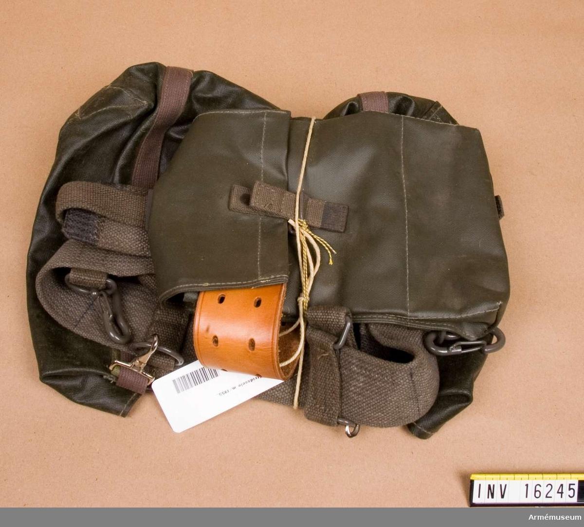 Stridssele m/1955.Av vaxduk med brunlila textilremmar är den större väskan, den mindre väskan stängs med gröna textilband. Sele av textil.