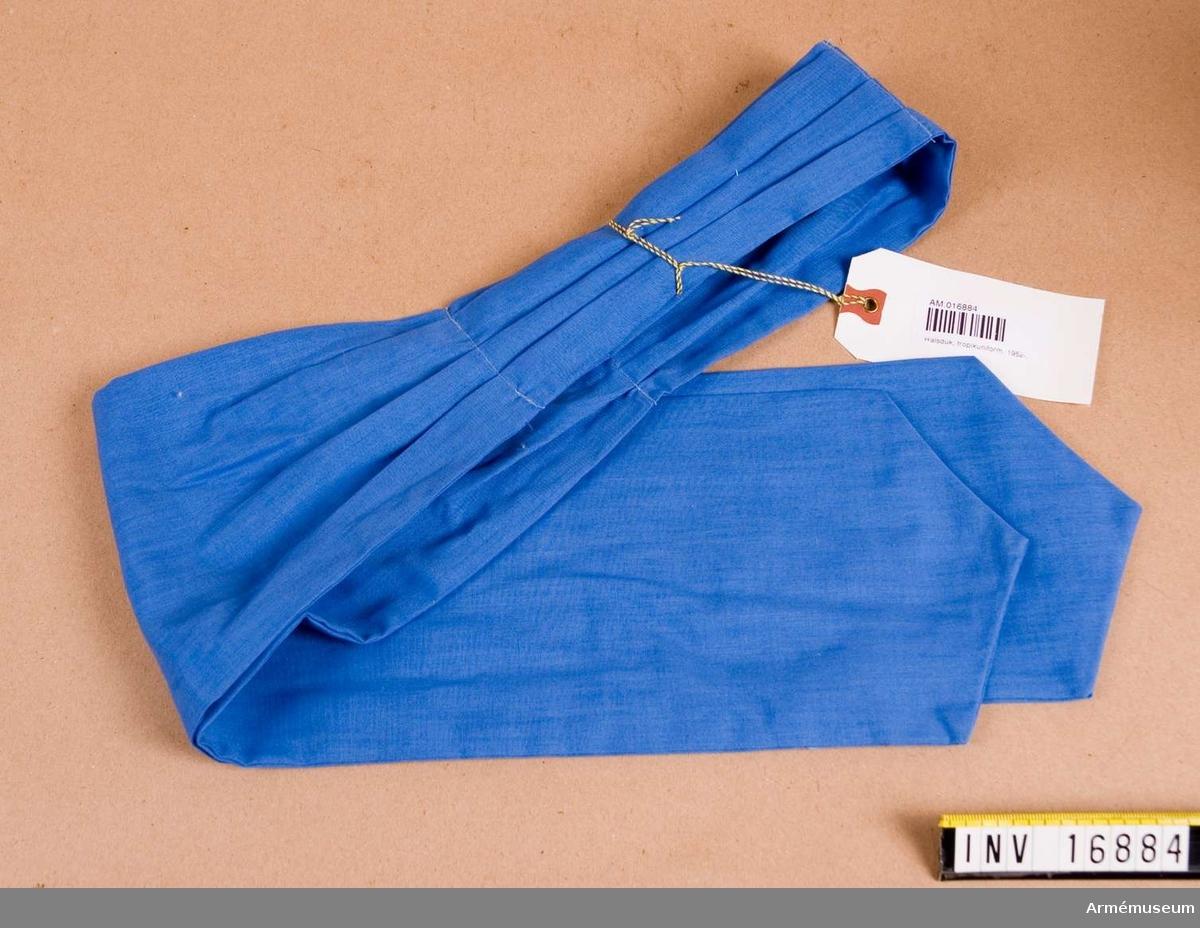 """Av blått bomullstyg, taget dubbelt och sydd i spets i de båda ändarna. I """"nacken"""" är tre veck lagda och tillhållna med en maskinsöm. Av Förenta Nationerna tillhandahållen halsduk. Källa: Uni A 1977."""