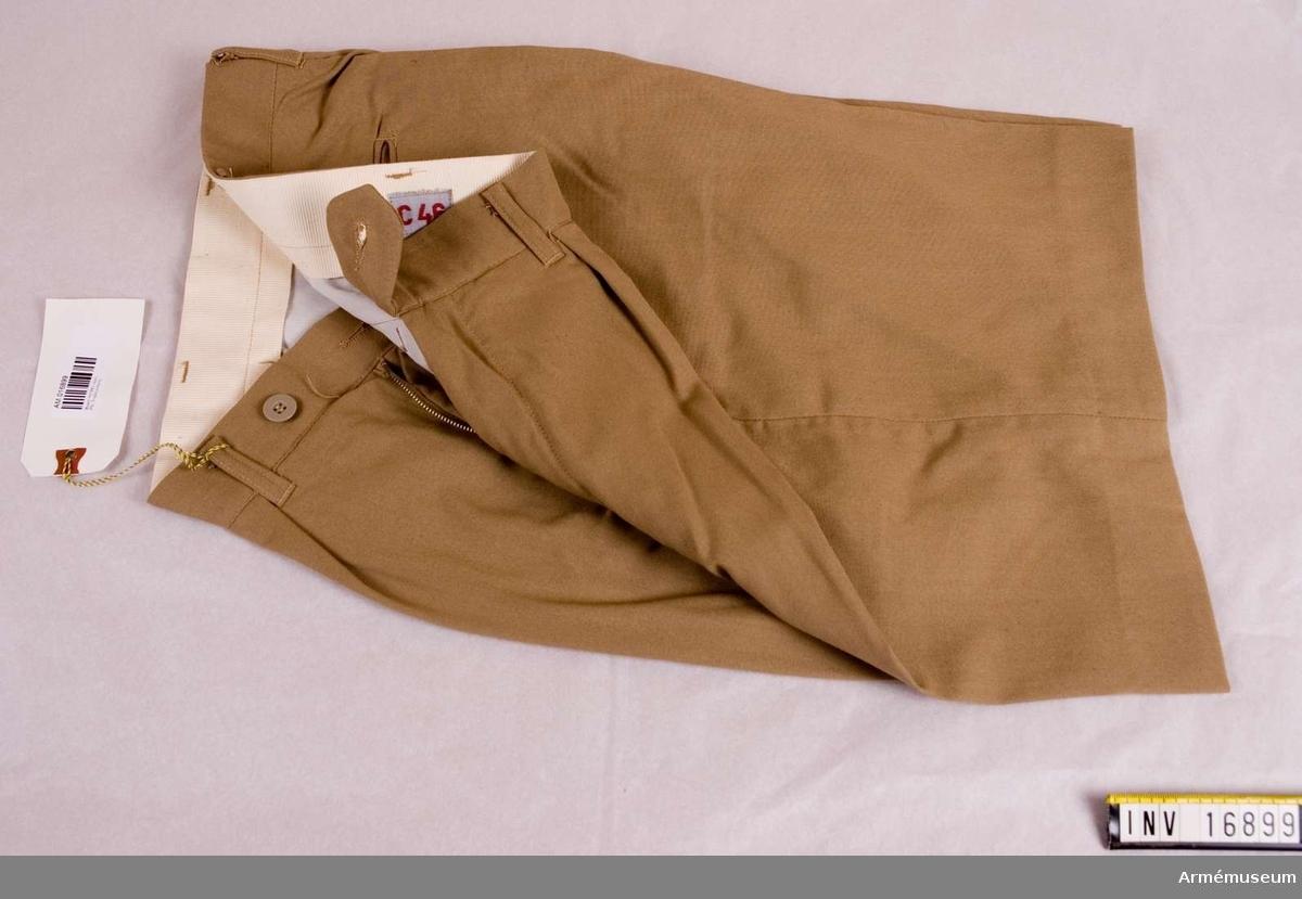 Kortbyxor m/1961, Tropikuniform. Av beigefärgat tyg. Har ett förlängt, löst midjeband med knapp och knapphål, blixtlås  i jylfen. Har sid- och bakfickor, varav de senare med knapp och knapphälla. Byxorna har hällor för livrem men saknar  hängselknappar. Storlek C 46. Ingår i uniform m/1961, tropikuniform, för alla försvarsgrenar och används vid utlandstjänstgöring.