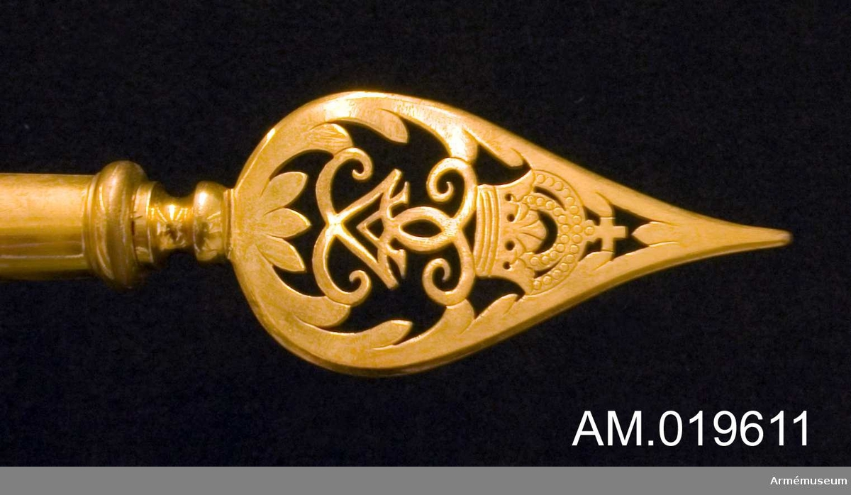 Spetsen är tillverkad av förgylld mässing. Den har Gustav V:s spegelmonogram under en kunglig krona inom ett bladverk som avslutas i en spets. Spetsen är försedd med en skruv. Spetsen tillhör fana AM 19544.