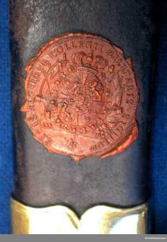 Grupp D II. Baljan är klädd med brunt skinn. Den har munbleck, mittbeslag och släpsko av förgylld mässing. De båda förstnämnda beslagen har var sin koppelring. Öglorna för koppelringarna sitter ej mitt på beslagens ryggar utan vid utsidan. På munbleckets ögla är siffran 3 inslagen. Längs nedre och en del av den främre kanten är släpskon skodd med stål. Mellanbeslaget och ringöglorna har vid båda ändar och munblecket längs sin nedre, släpskon längs sin övre kant en ingraverad rand, varjämte alla ovan omtalade kanter är prydda med 2 utbuktningar och mellan dem med en utskjutande flik. På baljans utsida finns rester av en påklistrad papperslapp och dessutom Krigskollegii sigill i rött lack