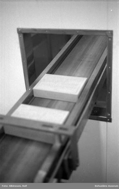"""Enligt fotografens noteringar: """" ... visar kartongerna kommer till Erik Flatting från rummet intill. Rätt ordning skulle varit 230, 228, 229. Erik kallar denna station för """"gratängpacket"""". ( AC. Fortsättning från bild 227). Fototid: 1996-01-19."""