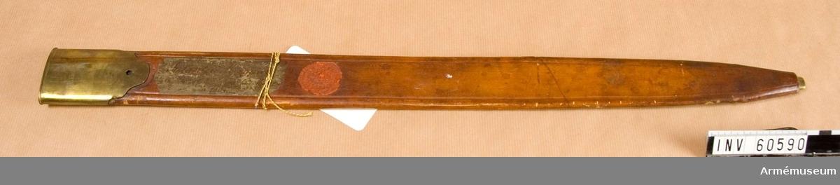 """Grupp D II. Baljan är av brunt läder och har doppsko samt munbleck av mässing. Doppskon täcks nästan helt och hållet av lädret.  Den på munbleckets utsida anbringade koppelhaken eller koppelknappen  är förkommen.  På en vid baljans utsida fastklistrad lapp står: """"Infanteri Huggare, hemsänd af Konungen från München år 1804."""" Dessutom är på samma sida Krigskollegiums sigill i rött lack anbringat."""
