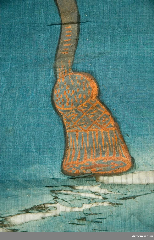 Duk Tillverkad av blå sidentaft. Sydd av två horisontella våder. Duken fäst med en rad tennlickor på ett gult sidenband. Bandet fortsätter ned i spiral runt stången.  Dekor: Målad, omvänt lika på båda sidor - Västerbottens sköldemärke: en ren i silver med gyllene horn, röd tunga, tre stycken sexuddiga silverstjärnor, upptill sammanbundna i en rosett med långa tofsprydda ändar i orange. Blad i silver och grönt, bär i orange.  Stång: Tillverkad av furu, mörkt brunmålad. Avsågad. Förlängd med en kopparhylsa. Holk av förgylld mässing.  Jämför AM.068224 (17203) och 28215.