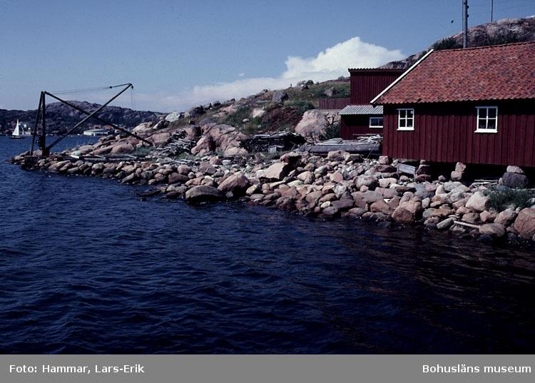 """Motivbeskrivning: """"F.d varv i Skredsvik, Bottnafjorden. Varvet drevs av båtbyggare Johan Jonasson fram till år 1942 och av Karl Johansson 1942-1975."""" """"På bilden syns till vänster till vänster båtbyggarverkstad, till vänster virkesmagasin. Till vänster kran tillhörande varvet."""" Datum: Juli 1980."""
