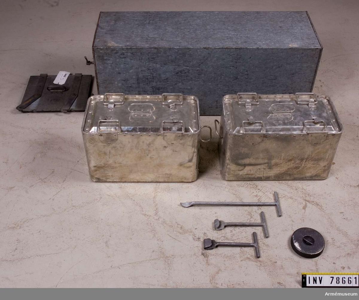 Grupp: I. III Isolerlåda med dubbla väggar av plåt. Lådan öppnas på ena kortsidan. Inuti finns plats för två kokkittlar på två värmeplattor av järn. KTS 2012-01-10  bestående av: 1. isoleringslåda med lock 2. kittel med lock 3. grytlock 4. järnlod 5. krok för järnlodens lyftande 6. skål för värmelod