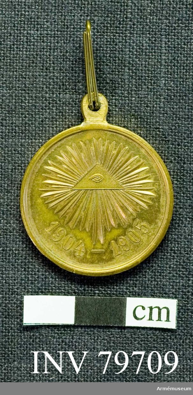 """Grupp M.   Medaljen har överst en fastlödd, massiv ögla, genom vilken bandhållaren är trädd. Åtsidan upptages till största delen av en triangel, innehållande """"det allseende ögat"""", omgivet på alla sidor av ett stort antal strålar av olika längd.  Ytterranden är dubbel och upphöjd. Å frånsidan, med enkel upphöjd rand läses: (okända bokstäver, se katalogkortet) (lär vara ett bibelspråk) på 5 rader. Bandet är i längdriktningen till hälften terracottarött; den andra hälften har 3 svarta och 2 orangefärgade smala ränder."""