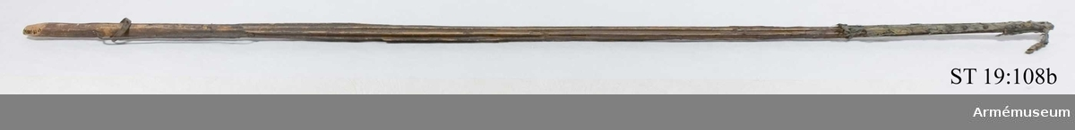 Stång av furu med spår av mörk färg. Rester av standarduk av blå sidendamast.