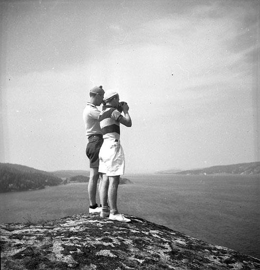 Två män i basker och shorts som står på Bodeleberget, Uddevalla, och ser ut över farleden