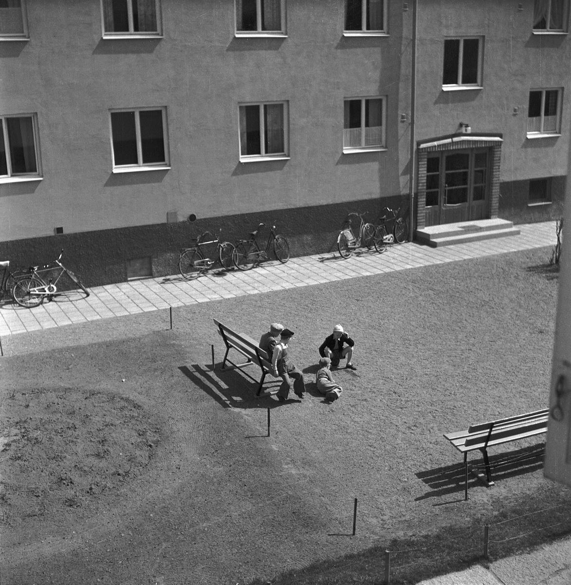 Fyra barn på en gård vid ett hyreshus i Jönköping. Två av dem spelar luffarschack på grusplanen och två sitter på soffan intill och tittar på. Några cyklar står lutade mot husväggen.