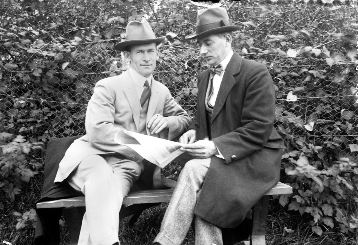 Två män sitter på en bänk, den ene läser en tidning. I bakgrunden syns buskar och ett stängsel.