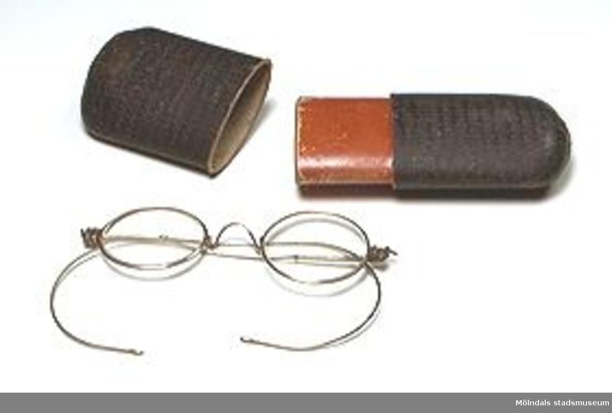 Glasögon med fodral av papp. Glasögonen har ärvts från givarens farfar och farmor i Tidaholm.