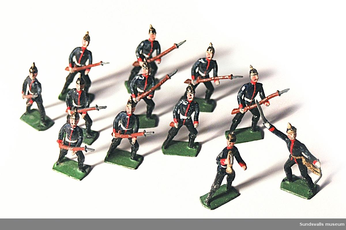SuM 2755:1-12 tennsoldater. Tio stycken med höjda gevär, en stycken med höjd sabel och en stycken med trumpet. Originalförpackning märkt 'G H made in Germany'.