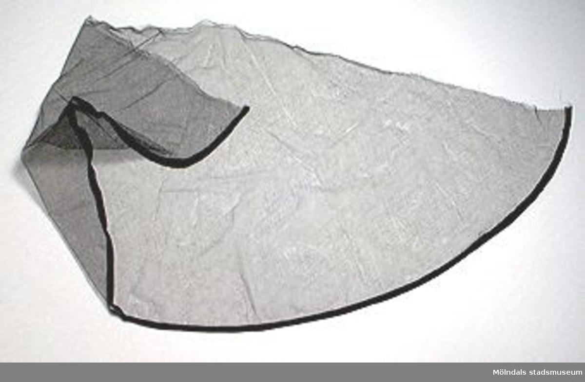 Fyra stycken sorgplagg. MM2260:1 Sorgflor, cirkelrunt, diam. 760 mm med två parallellgående fållar runtom. Den ena inre fållen har prydnadsfunktion.:2 Sorgslöja, halvcirkelformad, diam. 950 mm, fållad längs cirkelbågen.:3 Sorghalsduk. L: 1440 mm. B: 370 mm.:4 Sorgsjal. L: 1220 mm. B: 890 mm. Förvaras tillsammans i pappersask (240 x 250 x 50 mm). Tidigare sakord: sorgkläder.