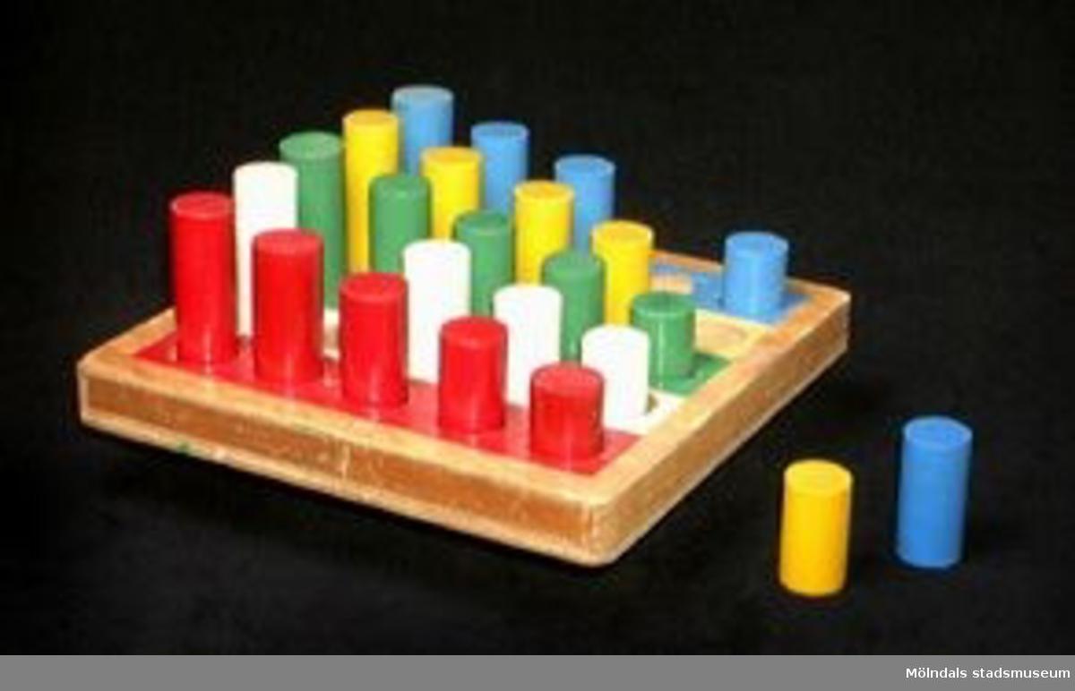 Spelbricka i trä med olikfärgade parallella fält med fem uppborrade hål i varje färgfält.Tillhörande: 24 träpikar (i fallande färger) Diam: 22 mm. L: 38 - 68 mm. En vit träpik (L: 60 mm.) saknas dock.Tidigare sakord: leksak.