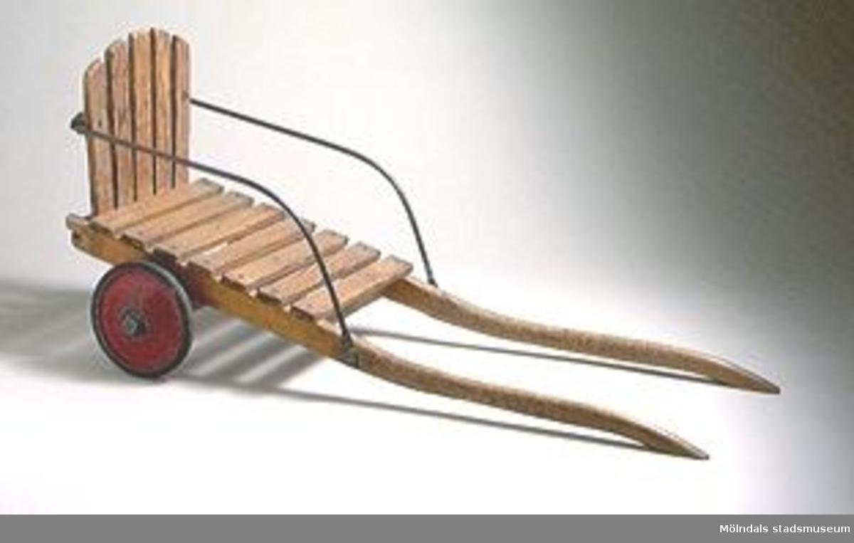Åkkärra helt av trä med två hjul och medar, gummi saknas på ett hjul.Gåva från Holtermanska daghemmet.