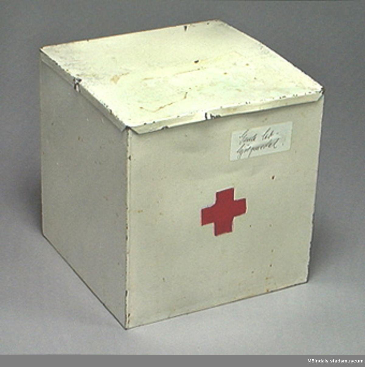 Vitmålad plåtlåda med lock.  På ena sidan är det målat ett rött kors.