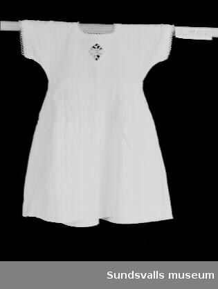 Vit flickklänning med kort ärm. Frivoliteter mitt fram, vid urringningen och på ärmarna. Knäppning i ryggen. Klänningen har ett avskuret liv och har lagda veck under detta.