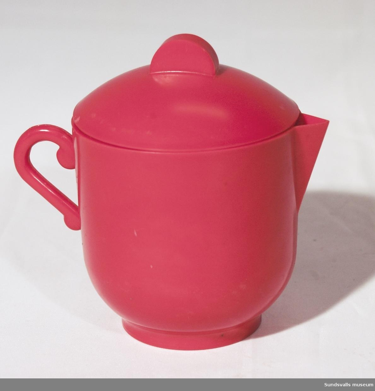SuM 5240:1-4 del av leksaksservis i röd plast. SuM 5240:1 kaffekanna med lock. Höjd 10,5 cm. SuM 5240:2-3 kaffekopp och fat. SuM 5240:4 kaffefat. Diam. 9,8 cm.