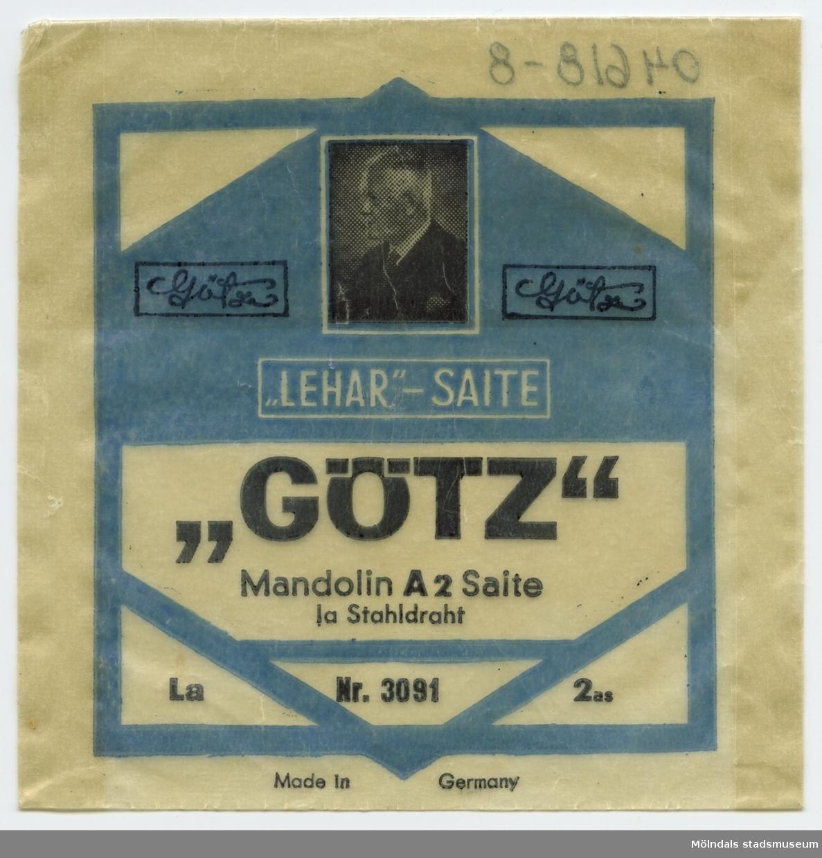 """Kläder och tillbehör till pappersdocka (som dock saknas) från 1950-talet, urklippta ur tidning. Fem set med lek- och sparkdräkter samt ytterkläder. En liten figur av papp, som troligen skall föreställa docka till pappersdockan, finns också tillsammans med kläderna, och är märkt """"Lenas"""" på baksidan. Kläder och tillbehör förvaras i ett kvadratiskt kuvert av smörpapper, med texten: """"'Lehar'-Saite, 'Götz', Mandolin A2 Saite"""", och har troligen ursprungligen innehållit mandolinsträngar."""