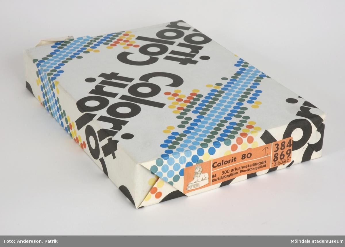 """500 st skrivpapper som är förpackade med ett omslagspapper från Papyrus i Mölndal.Omslagspappret är vitt och har småprickar i olika färger. Ordet  """"Colorit"""" finns också tryckt på omslaget.Det är lite uppsliet i kanterna.På sidan av förpackningen sitter en etikett med dessa uppgifter: """"Colorit 80 A4 500 ark/sheets/Bogen Klarblå/Klingfisher Blue/Königsblatt    384 869   435.692"""" + Papyrus loggan (en sfinx). Etiketten är orange. Texten är svart. Loggan är vit.Storlek på förpackning:Längd: 301 mm Bredd: 210 mmDjup: 50 mm"""