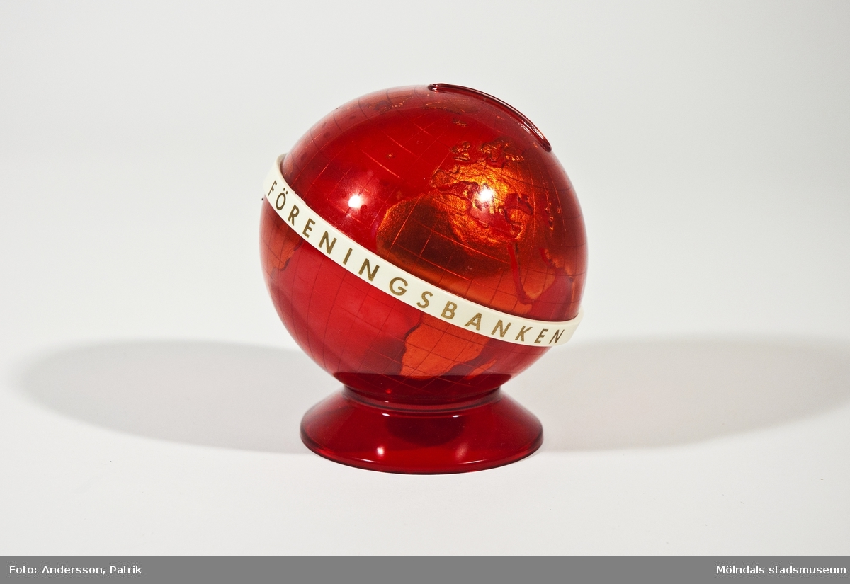 """Sparbössa i form av en röd jordglob från 1970-talet.Namnet """"FÖRENINGSBANKEN    YHDYSPANKEN"""" finns tryckt med guld bokstäver på en vit axel runt jordgloben.  Man öppnar sparbössan på undersidan. Där finns också """"MK Made in Finland by TRESMER OY"""" gjutet i plasten.MåttHöjd: 100 mm, Diam: ca. 85 mm, Omkrets: 310 mm"""