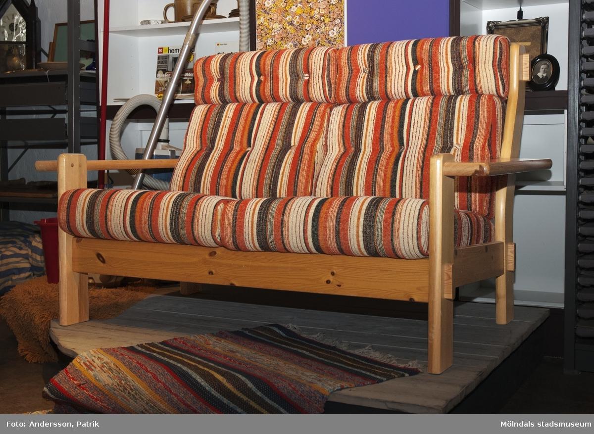 2-sits soffa från 1970-talet.Soffan har trästomme av furu. Sittdynan är av nopprigt tyg som är randigt i färgerna orange, rött, brunt, grått och vitt m.m.Dessa soffor var mycket vanliga i gillestugorna framförallt i mitten av 1970-talet och framåt. De köptes oftas i grupp, till exempel en 3-sitts soffa, 2-sitts soffa + fåtölj.MåttLängd: cirka 1500 mm, Djup: cirka 850 mm