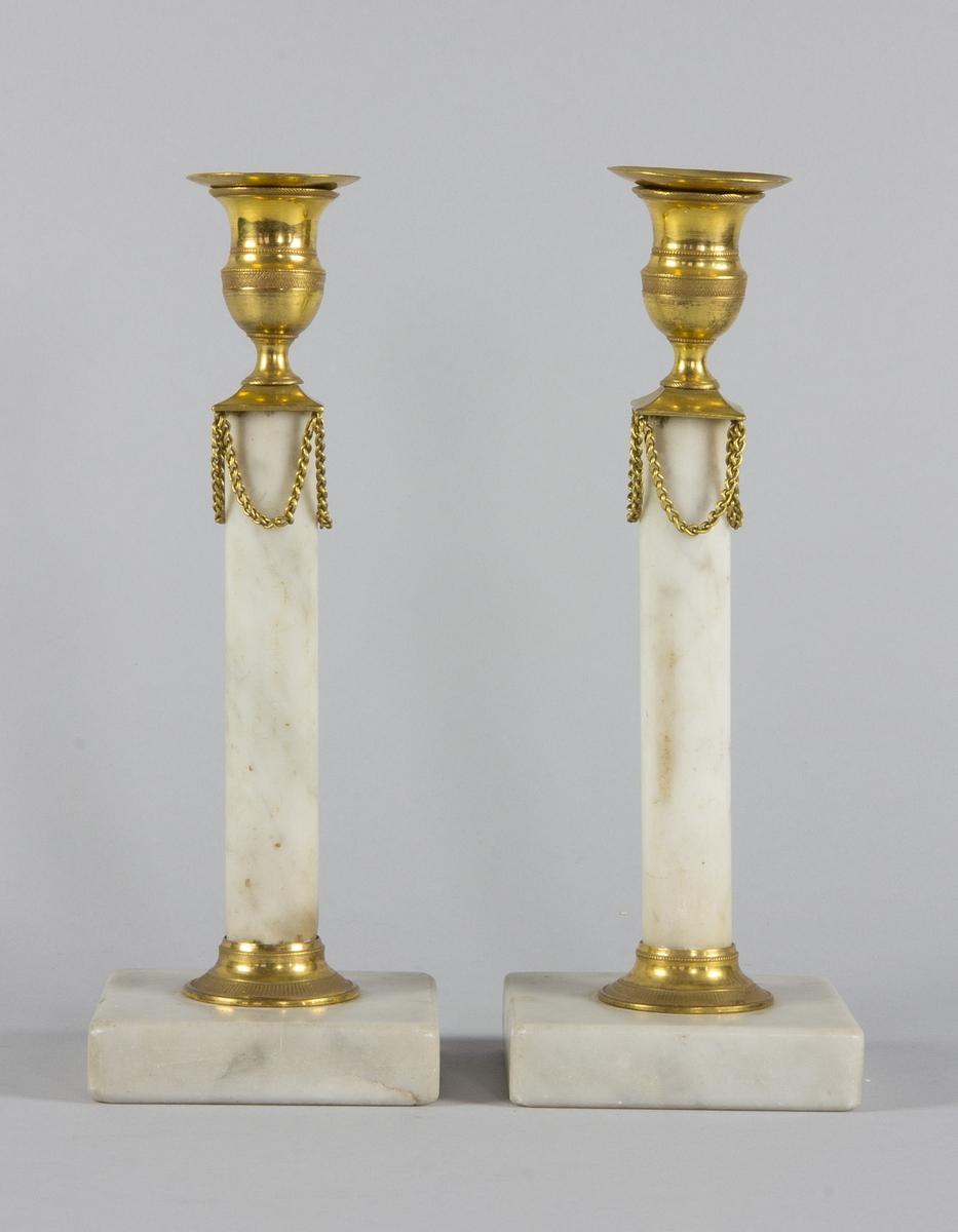 Ljusstakar, ett par, av vit marmor, med kolonnformade skaft på kvadratiska fotplattor. Med ljuspipor och beslag av brännförgylld brons. Beslagen i form av hängande kedjor. Med lösa ljusmanschetter av plåt.