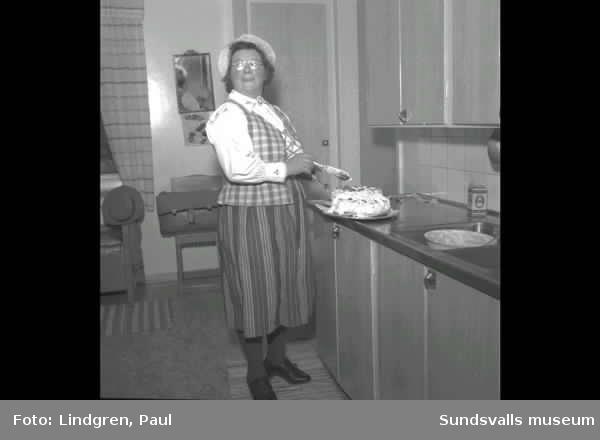 Musik hos Melander i Bydalen. Kvinnor i dräkter dukar upp tårta o kakor,