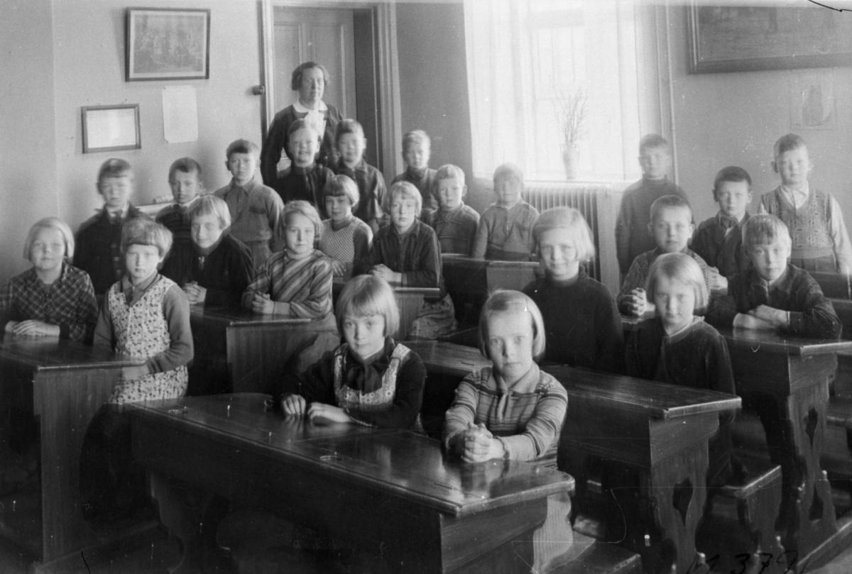 Gruppfoto av flickor och pojkar i klassrum i Kärra skola, samt lärare Emma Aronsson.