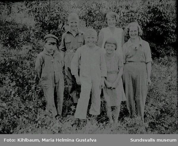 Grupporträtt. Kvinna med fem barn i utemiljö.