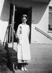 Kvinna, troligen sköterska, stående på trappan utanför ett h