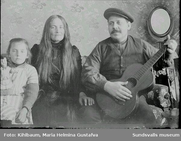 Familjeporträtt i rumsmiljö. Ester Näslund, Ljustorp, med föräldrar. Ester Näslund kom att arbeta som fotoassistent och senare fotograf i Maria Kihlbaums fotoateljé i Sundsvall.