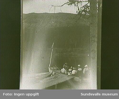 Kvinnor och barn i en båt på en fjällsjö.