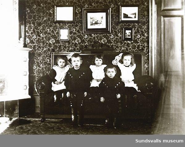 Grupporträtt. Fem barn i en soffa i rumsmiljö.