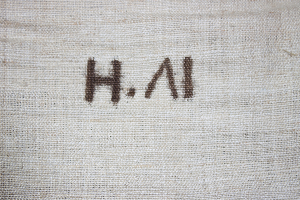 Madrass, tillverkad av grovt lingarn, maskinsydd. Modell med sidostycken och stickade sömmar. Puskor av tygbitar i flera färger och kvaliteter. Märkt med brunt tusch: IV'H eller H.(omvänt V)I.  Fyllning: halm.