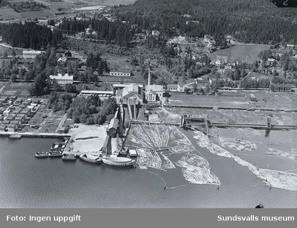 Vy av Tunadals sågverk och hamnområde.I bakgrunden jordbruksbebyggelse.