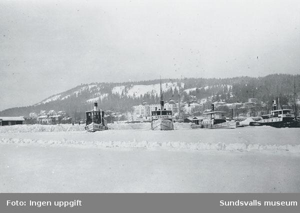 Bogserbåtar på rad infrusna i Sundsvalls hamn.