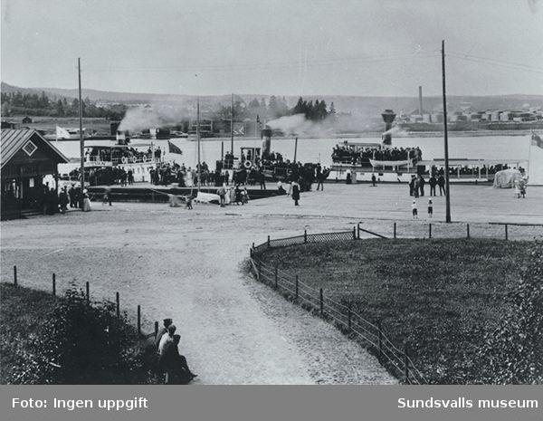 """IOGT:s utflykt till Skönvik. På bilden tre båtar varav en med namnet """"DUFVAN""""och en av båtarna bär unionsflaggan. I bakgunden sågverk."""