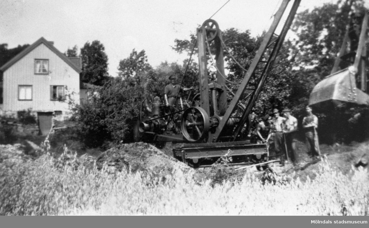 Nedanför Hällesåker mot Lindome, står detta mudderverk och gräver ut Lindomeån, 1930-talet. Beställningsarbete av August Werners fabriker. Mudderverken är troligtvis tändkulemotorer fabrikat Skandia.
