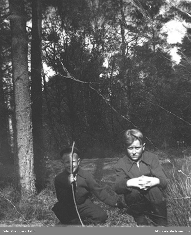Bröderna Alf och Leif Garthman sitter på knä vid ett skogsområde i Balltorp. Början av 1950-talet.