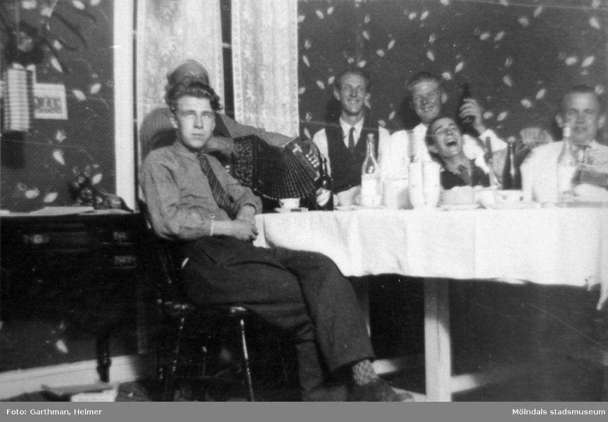 Fest i Fjärås Bräcka, 1930-tal. Sex män sitter samlade runt ett flaskfyllt bord. En man spelar dragspel och personen längst fram heter Bror Eriksson.