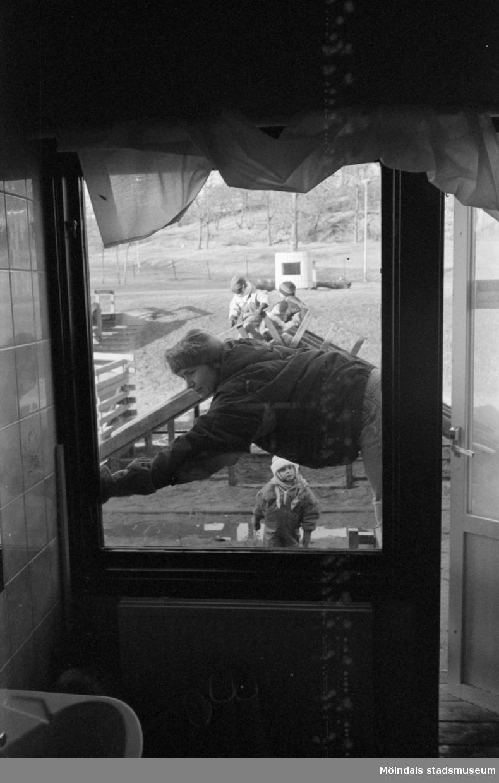 Bild fotograferad inifrån och ut genom ett fönster från Katrinebergs daghem. En balkongdörr till höger är lite öppen. Utanför syns en vuxen person med mössa som lutar sig över ett staket. Lite längre bort ses vinterklädda, lekande barn.