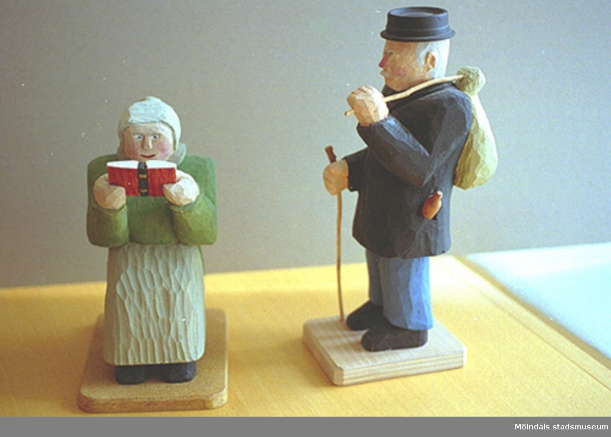"""En gråhårig, grönklädd kvinna sitter och läser i en bibel. Vid sidan av står en gråklädd man med hatt och käpp. Han har en kappsäck hängande över axeln. Harry Bergmans """"gubbar"""" (träfigurer)."""