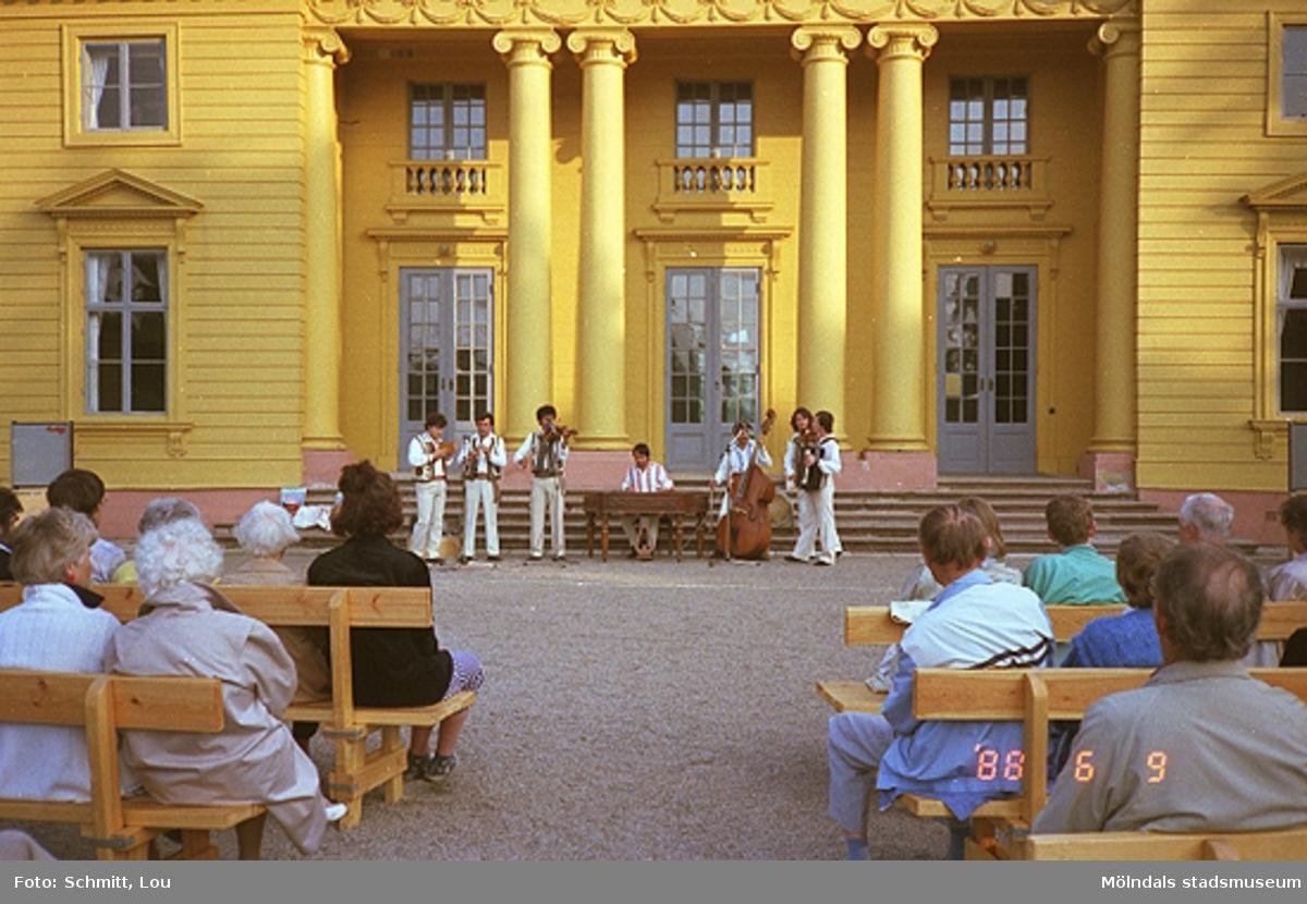En orkester, bestående av sju män, spelar musik inför publik på Gunnebo slotts framsida. Publiken sitter på bänkar.
