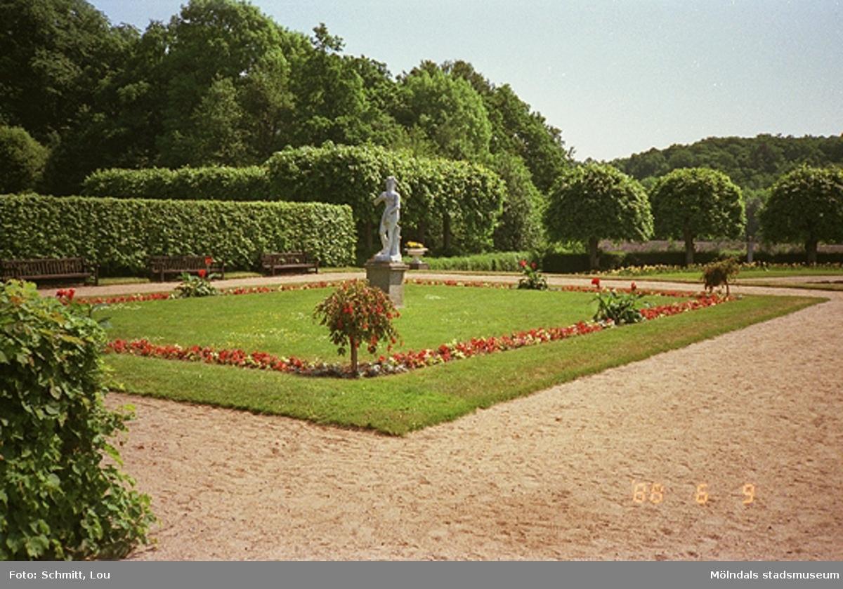 Gunnebo slotts baksida. Man ser en gräsmatta med en skulptur i mitten, kantad av blomrabatter. I bakgrunden ser man häckar och träd.