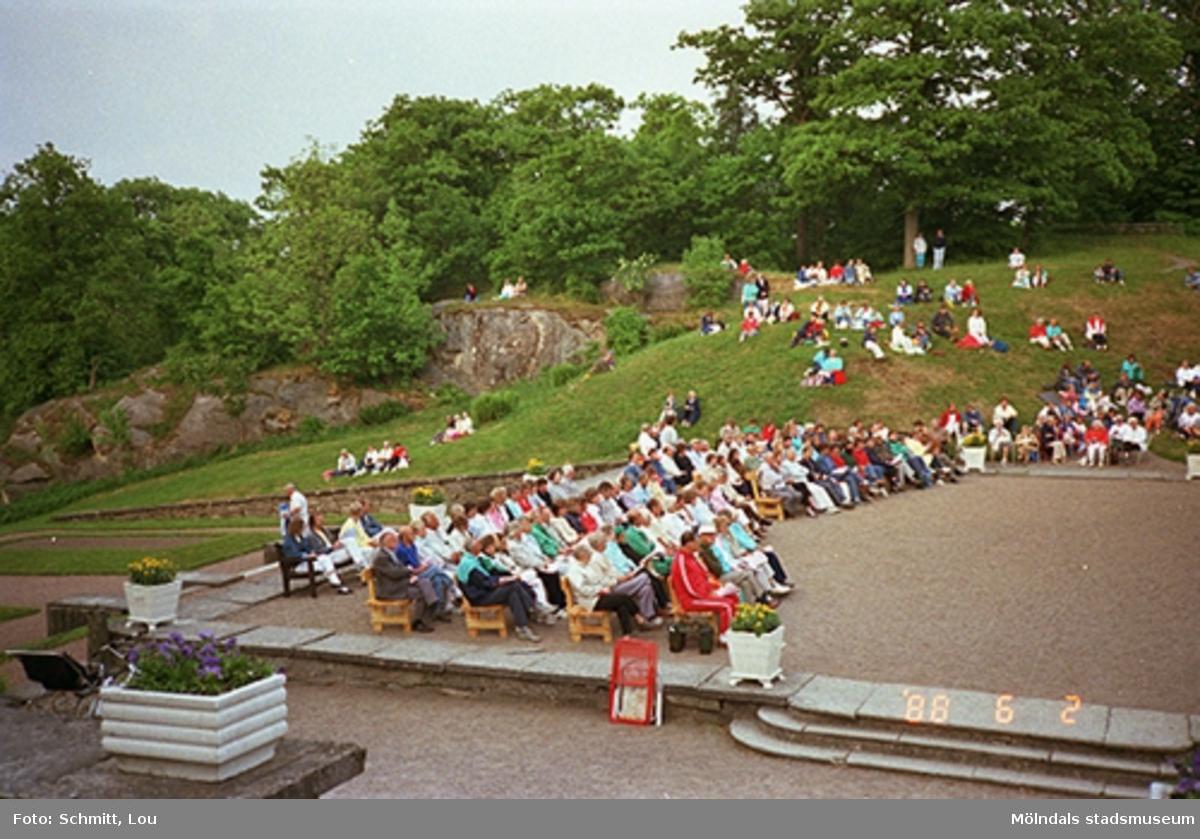 Människor som sitter och tittar på ett musik- och teateruppträdande på Gunnebo slotts framsida.
