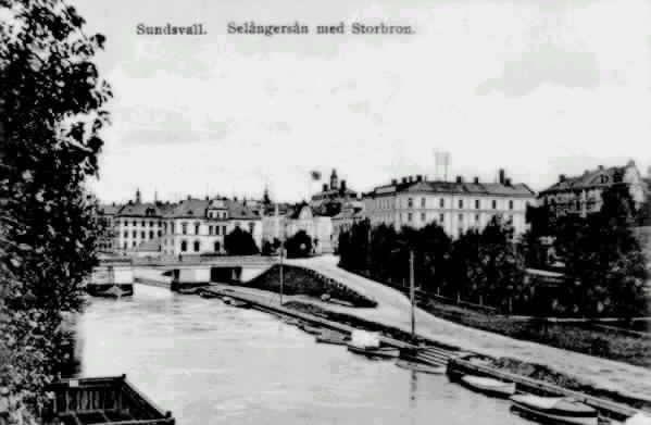 """Från vänster Storbron, kv Lyckan 1, kv Penningen 1/Riksbank. I förgrunden Selångersån till vänster vedpråm och till höger båtar. Text till bild """" Sundsvall. Selångersån med Storbron."""""""