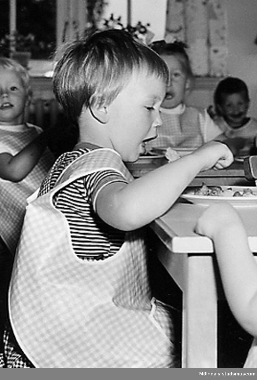 En flicka som äter mat på Holtermanska daghemmet 1953